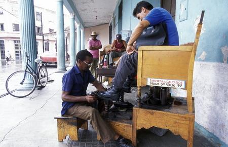 traditon: Ein Schuhputzer im Zentrum der Historischen Altstadt von Sancti Spiritus auf der Insel Kuba.       (Urs Flueeler)