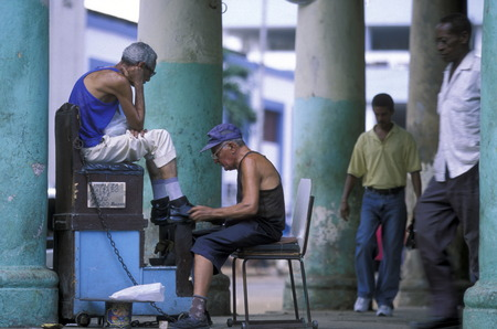 arbeit: a shoe cleaner in the city of las Tunas on Cuba in the caribbean sea. Editorial