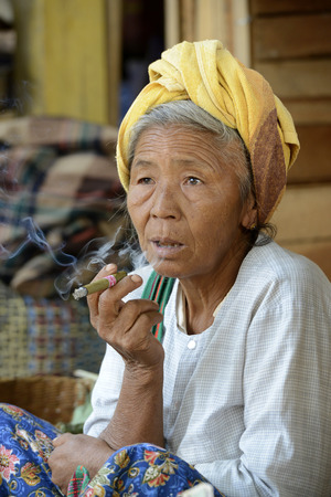 cheroot: a women smokes a cheroot cigar at the Market in the village of Ywama at the Inle Lake in the Shan State in the east of Myanmar in Southeastasia.