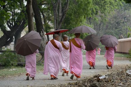 streetlife: Buddhist Nun on a road in the town of Nyaungshwe at the Inle Lake in the Shan State in the east of Myanmar in Southeastasia.