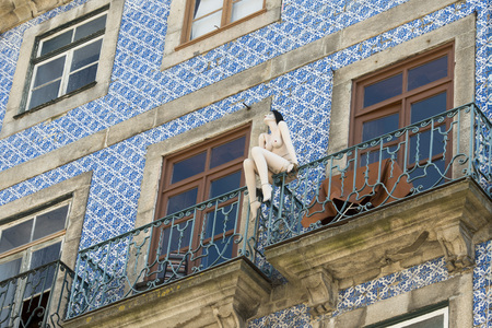 a naket women pupet on a balcony in Ribeira in the city centre of Porto in Porugal in Europe. Editorial