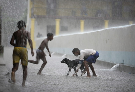 southamerica: childern play by rain in the town of chuao near choroni on the caribbean coast in Venezuela.