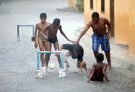 southamerica: childern play soccer by rain in the town of chuao near choroni on the caribbean coast in Venezuela.