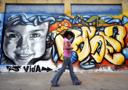 southamerica: people in a street with graffiti in the city of Valencia in the west of Venezuela.