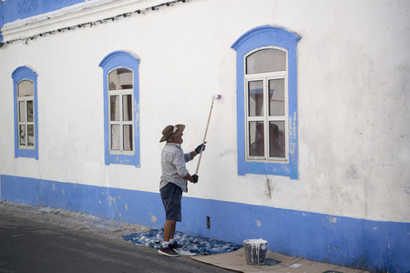 streetlife: a men painting his house in the Town of Cabanas near Tavira at the east Algarve in the south of Portugal in Europe. Editorial
