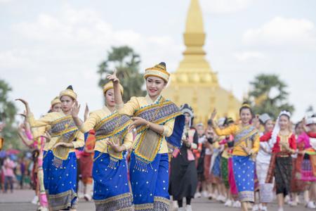 辻のラオスのビエンチャンの市内の Pha、ルアンの祭での式典での伝統的な衣装の人々。