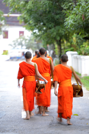limosna: monks in the morning in the town of Luang Prabang in the north of Laos in Southeastasia.