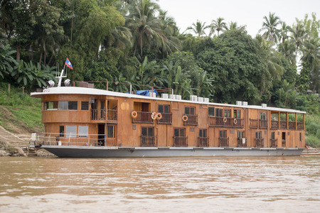a hotel boat or cruise boat at the Mekong River in the town of Luang Prabang in the north of Laos in Southeastasia.