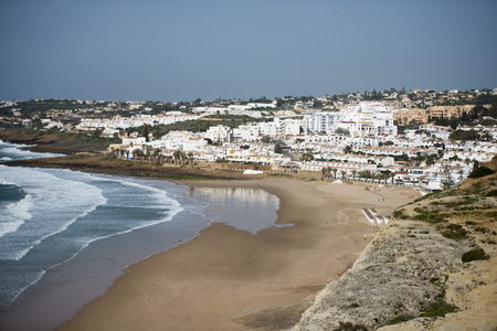 the beach with the village of Luz at the Algarve of Portugal in Europe. Stock Photo