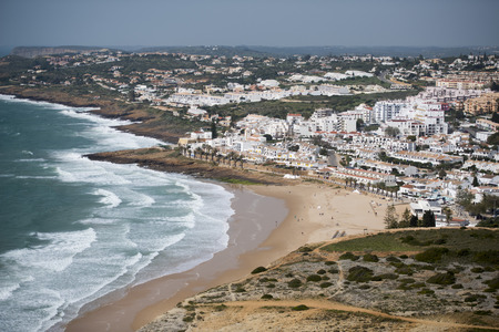 the beach with the village of Luz at the Algarve of Portugal in Europe. Banco de Imagens