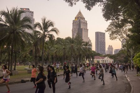 people at exercise at the Lumphini Park with the Skyline in the city of Bangkok in Thailand in Southest Asia.  Thailand, Bangkok, November, 2019