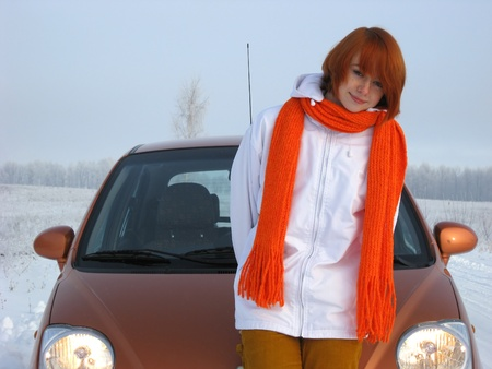 Red-haired girl and orange car on winter road photo