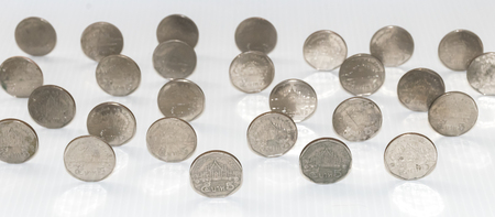 too many: Too many coins are standing on the white background. Stock Photo