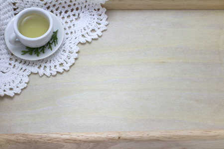 picture of cup of green tea and white doily on wood background photo