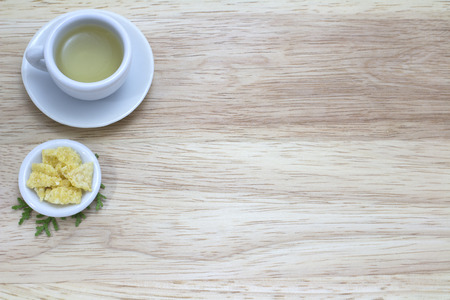 picture of cup of green tea and snacks on wood background photo