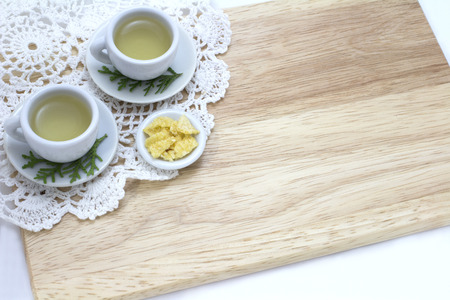 picture of two cups of green tea, snacks and white doily on wood background photo