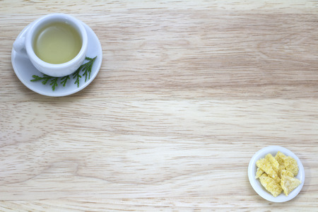 picture with cup of green tea with snacks on wood background photo