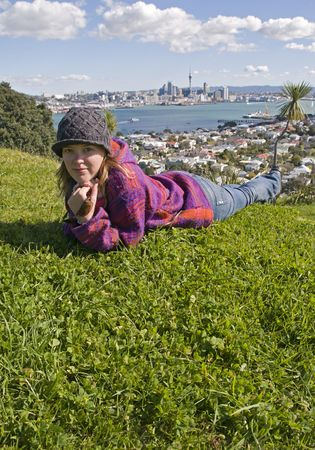 Adult Woman laying on the Grass at Victoria Mount, Auckland, New Zealand, photo