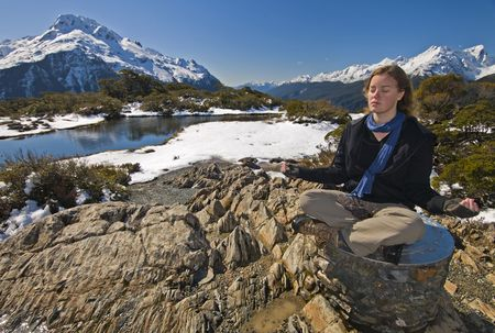 milford: Blonde woman meditating at Milford Sound in New Zealand.