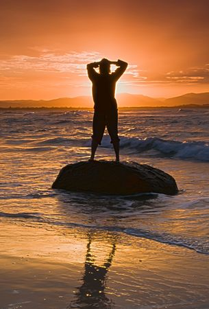Woman with her hands on her head as the sun goes down. photo