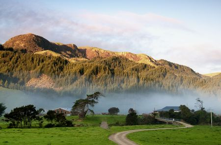 Colville Farm with mist  moving through at sunset on Coromandel peninsula, New Zealand
