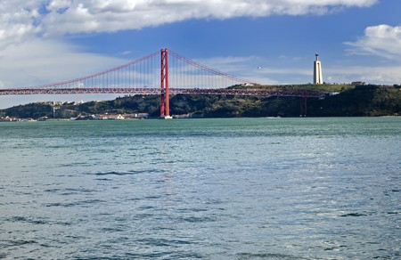 The 25th of April Suspension Bridge in Lisbon, Portugal. Captured from the Tagus River with the Statue of Christ (Cristo Rei)  in the distance. photo