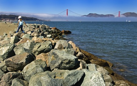 Morning Mist covers the Golden Gate Bridge as a little girl plays in the rocks. Stock Photo - 7526592