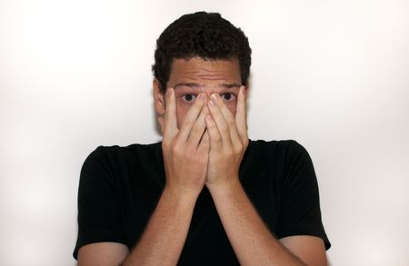 Young man covering his face in fear on isolated background photo