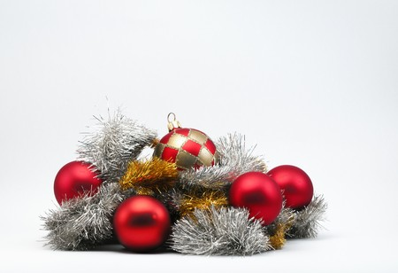 Christmas baubles in silver & gold tinsel on a white background