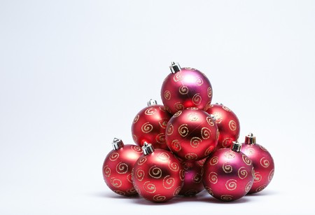 Pile of red Christmas Baubles with gold glitter on a white background. (Selective Focus)