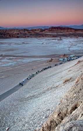 Tourists returning to their transportation after watching the sun setting at Moon Valley in the desert of Atacama, Chile  photo