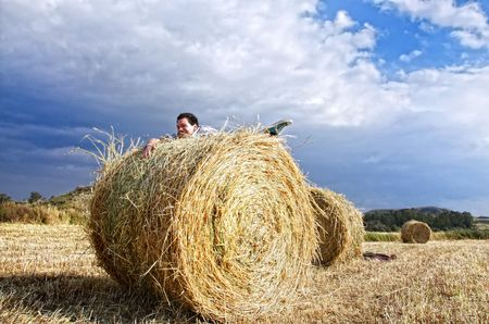 Man trying to hold up on haystack in the fields photo