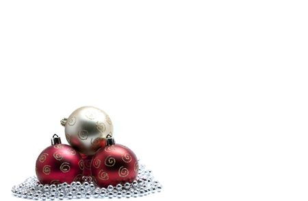 Gold christmas bauble on three red baubles with glitter on silver beads photo