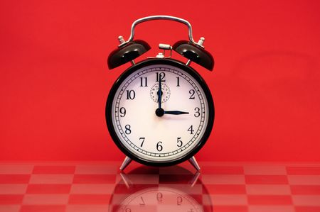 Vintage Alarm Clock Showing 3 OClock Isolated on a Red Background. photo