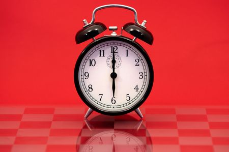 Vintage Alarm Clock Showing 6 OClock Isolated on a Red Background. photo