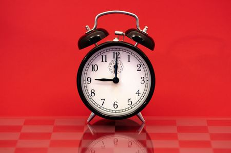 Vintage Alarm Clock Showing 9 OClock Isolated on a Red Background. photo