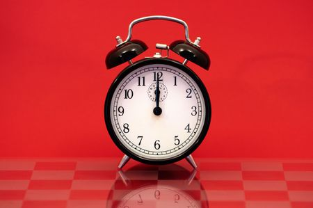 12 oclock: Vintage Alarm Clock Showing 12 OClock Isolated on a Red Background.