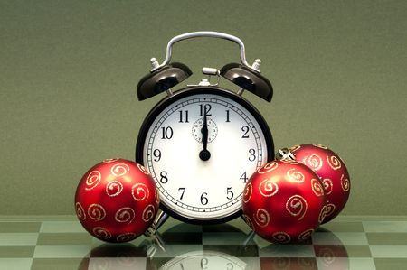 12 oclock: Vintage Alarm Clock Showing 12 OClock Isolated on a Green Background with three Christmas Baubles.