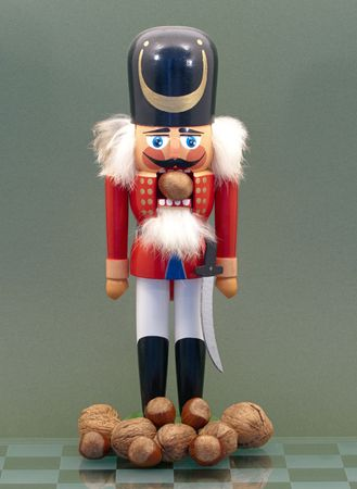 Wooden Nutcracker with Nuts Isolated on a Green Background. photo