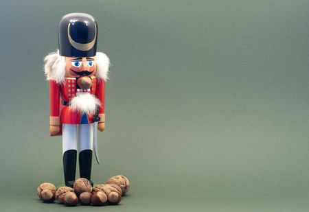 Wooden Nutcracker with Nuts Isolated on a Green Background. Stock Photo