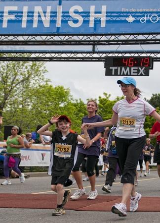 Competitors cross the finishing line of the 2011 Ottawa 5km Race, May 28 2011, Ottawa, Canada.