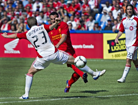 Liverpool's Spanish full-back Jose Enrique takes a shot at goal despite the attention of Toronto FC's Terry Dunfield in Liverpool's first pre-season match of their North American tour against Toronto FC at the Rogers Centre in Toronto, Canada, July 21 201