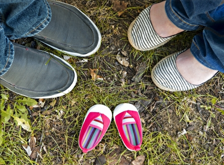 Pink baby shoes between the feet of the parents-to-be.