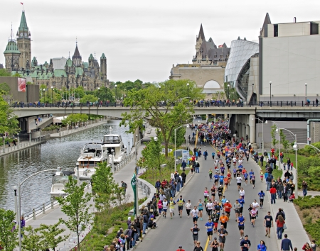 rideau canal: Runners pass along the Rideau Canal during the 2013 Ottawa Marathon in Ottawa, Canada with Parliament Hill in the distance on May 26 2013. Editorial