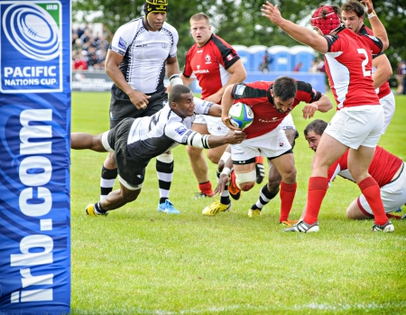 fijian: Fijian player Leone Tabuarua grabs on to Canadas Phil Mack during the IRB Pacific Nations Cup match held at the Twin Elm rugby park in Ottawa, Canada on June 5, 2013.