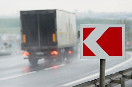 sharp curve: Red and white road alarm sign near sharp turn. Motion-blurred truck on backround.