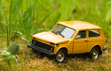 suv: Yellow toy SUV car on green grass