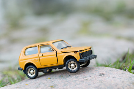 Close up image of yellow toy SUV outdoors Stock Photo