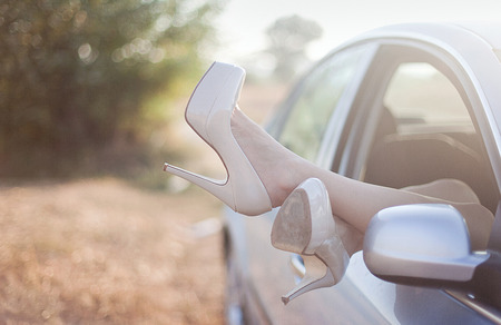 high heels: Sexy woman legs on high heels out the windows in car Stock Photo