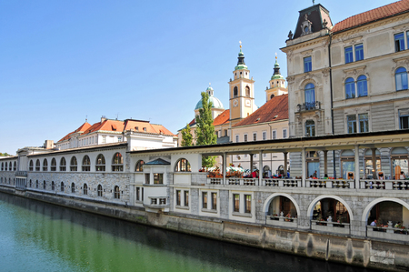 st  nicholas cathedral: Ljubljana, Slovenia - September 1, 2015 - Ljubljanica river and St. Nicholas cathedral in the background on a bright sunny day